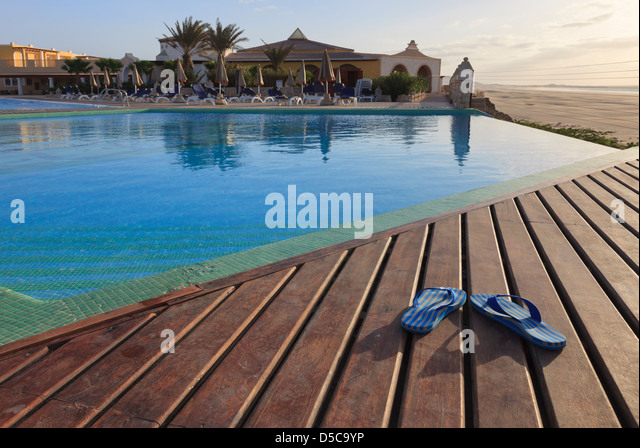Pair of flip-flops on sun decking by empty infinity pool in luxury holiday resort hotel on Boa Vista Island, Cape - Stock-Bilder