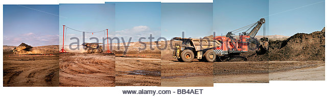 Gigantic dump trucks drive away after being filled with oil sands in northern Alberta at the Syncrude Aurora mine. - Stock Image