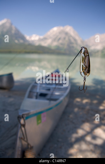 A close-up of a fishing lure with a canoe and mountains in the background. - Stock Image