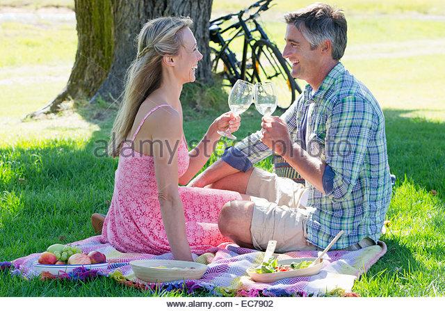 Couple drinking wine sitting on picnic blanket - Stock-Bilder