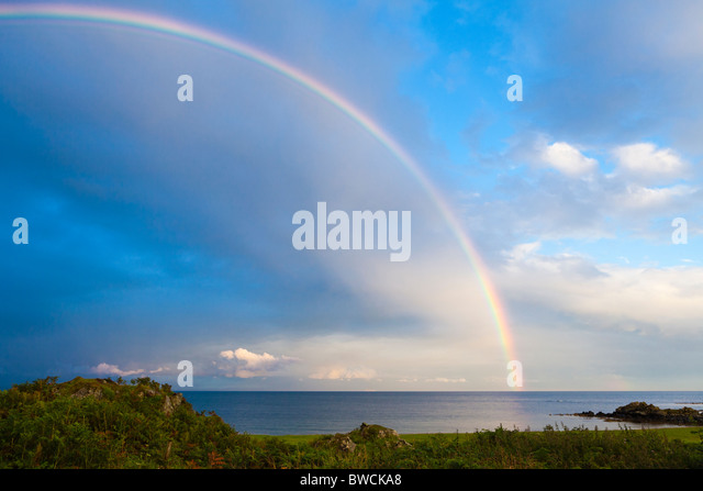 A rainbow at sunset over the Kilbrannan Sound, east of the Kintyre peninsula, from near Peninver, Argyll & Bute, - Stock Image