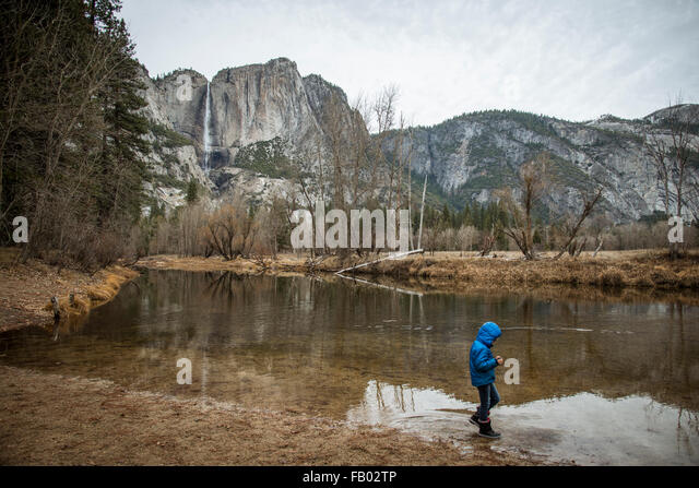 Young child  walking the edge of the river in Yosemite Valley in fall.Wearing a blue winter coat with hood. near - Stock Image