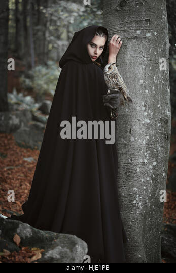 Forest keeper with black cloak and grey owl. Fantasy and legend - Stock-Bilder