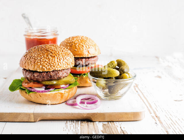 Two fresh homemade burgers, pickles, ketchup and onion rings on white wooden serving board - Stock Image