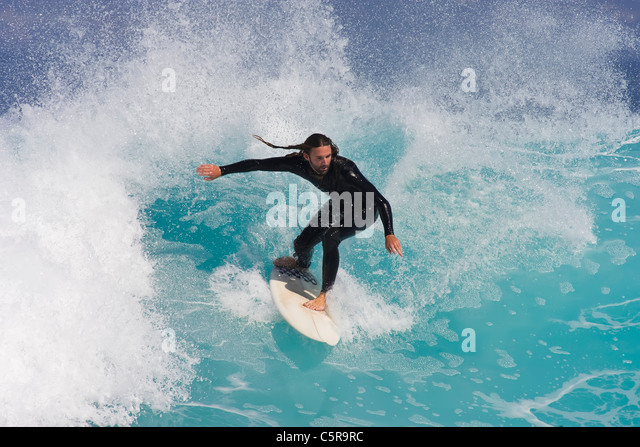 Surfer balanced riding beautiful blue wave. - Stock Image