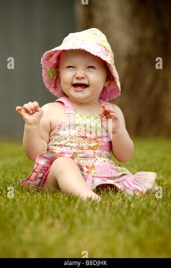 Laughing toddler wearing sunhat, seated on green grass, Saskatechewan, Canada - Stock Image