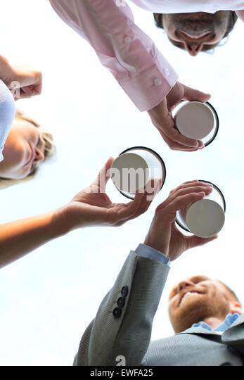 Directly below shot of businesspeople holding disposable cups against clear sky - Stock Image