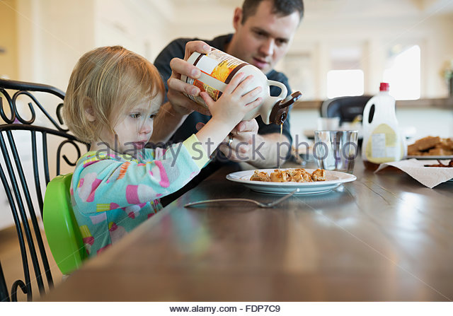 Father helping daughter pour maple syrup on waffles - Stock Image