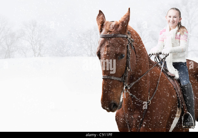 USA, Illinois, Metamora, Smiling girl (10-11) riding horse during winter - Stock Image