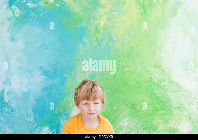 Young boy sitting in front of green and blue painting - Stock-Bilder