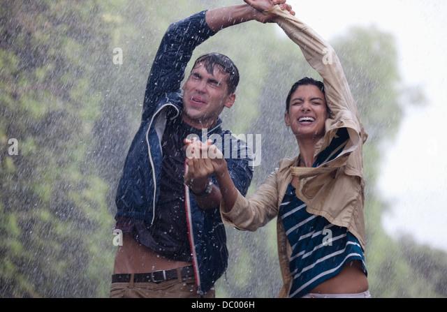 Happy couple dancing in rain - Stock-Bilder