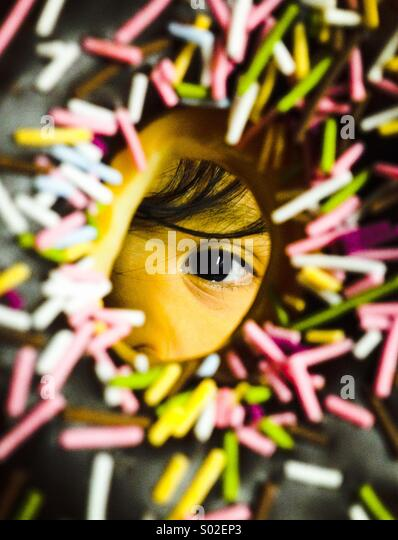 4 year old Rio S. Of Japan looks through a doughnut as he gets ready to eat it. - Stock Image