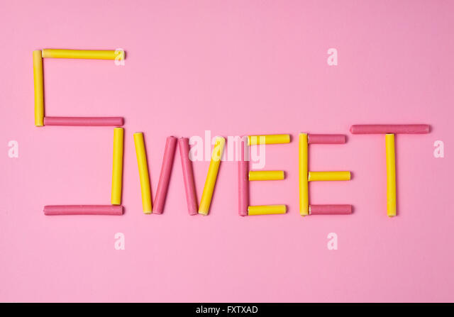 yellow and pink coated marshmallows forming the word sweet on a pink background - Stock Image