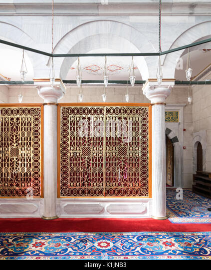 Golden ornate perforated partition framed in white marble arch and ornate carpet at Fatih Mosque, Istanbul, Turkey - Stock Image