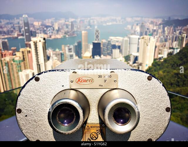The binoculars point toward the city of Hong Kong from the Sky Platform at Victoria Peak. - Stock Image