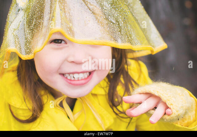 Girl wearing yellow rain coat and hat - Stock Image