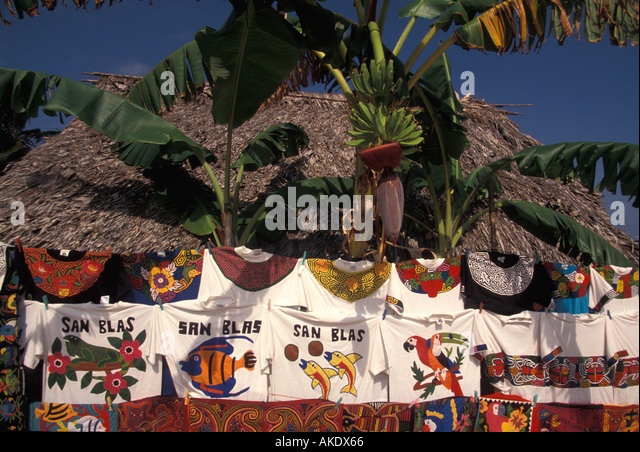 Republic of Panama cuna indians san blas islands mola t shirts hanging on clothesline under coconut palm tree fronds - Stock Image