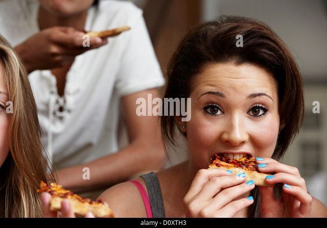 Teenage girl eating pizza - Stock Image