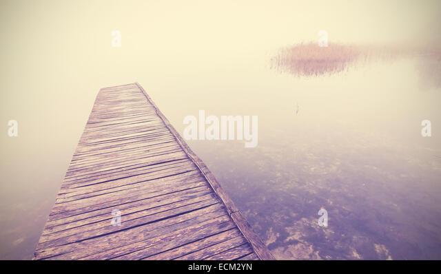 Retro filtered picture of old wooden pier into dense fog. - Stock-Bilder