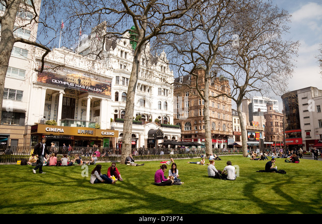 People sitting enjoying the sunshine in spring, Leicester Square, Central London WC2, UK - Stock Image