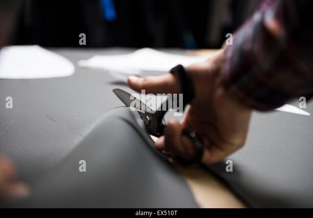 Man Cutting Wet Suit Fabric with Scissors - Stock Image