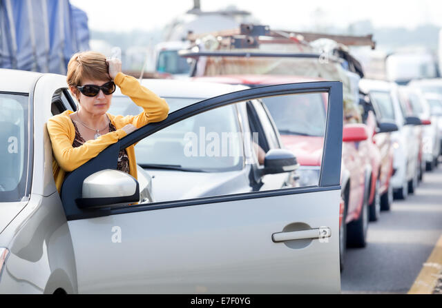 Frustrated middle aged Hispanic woman stuck in a traffic jam. - Stock Image