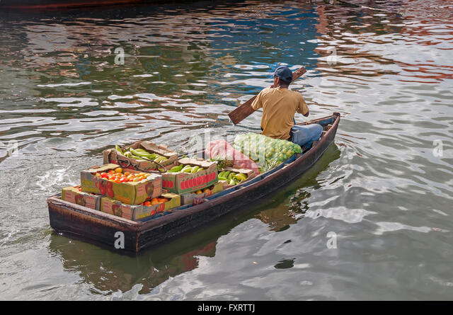 Man paddles skiff loaded with fruit from the floating market, Willemstad Curacao - Stock Image