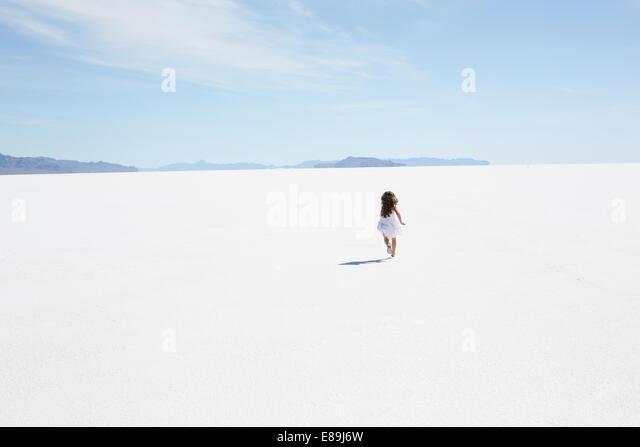 Girl running along Bonneville Salt Flats - Stock-Bilder