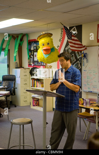 A California middle school Spanish teacher in a classroom decorated with a pinata. - Stock Image