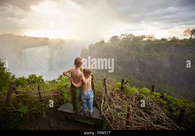 Two young boys standing on ledge admiring the view, rear view, Victoria Falls, Livingstone, Zimbabwe - Stock Image