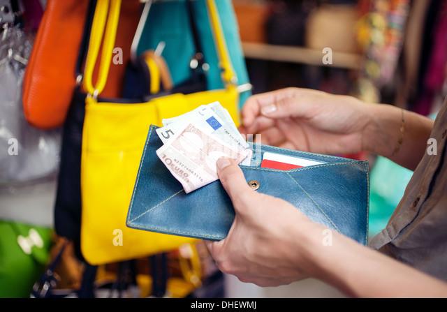 Young woman buying handbag, San Lorenzo market, Florence, Tuscany, Italy - Stock Image