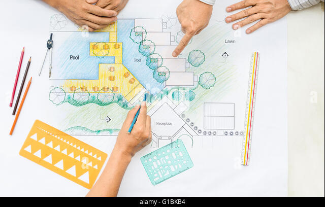 Landscape architect changing drawing at meeting with client - Stock Image