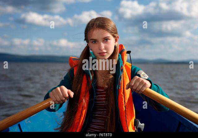 Caucasian girl rowing canoe in lake - Stock Image