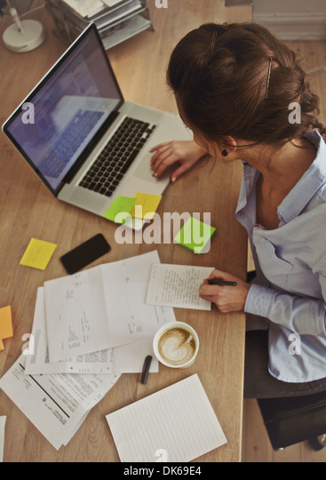 Overhead view of young brunette using laptop while at work. Businesswoman working at her desk. - Stock Image