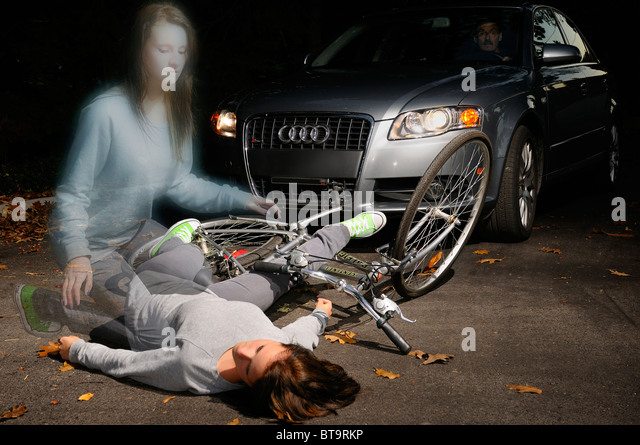 Fearful man in car stopped at a fallen young female bicyclist dead on the road with her ghost spirit rising from - Stock Image