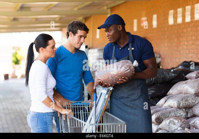 African hardware store salesman assisting customers in buying garden stones - Stock Image