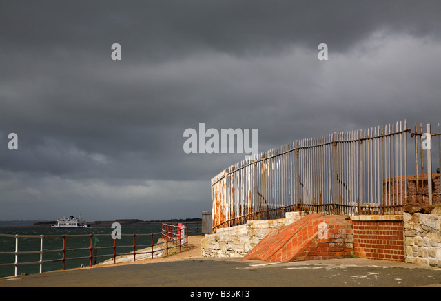 rusty and corroded railings and broken brickwork on the Portsmouth coast against a dark stormy sky - Stock Image