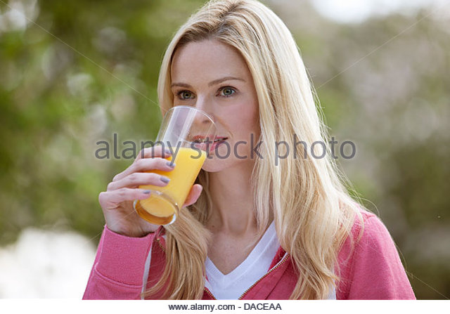 A young woman drinking a glass of orange juice outside - Stock Image