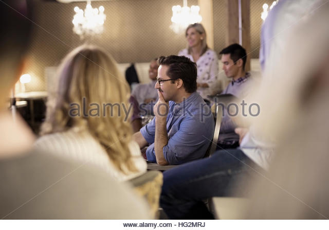 Attentive businessman listening in conference audience - Stock Image