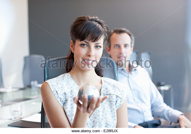 Businesswoman  holding small globe in conference room - Stock Image