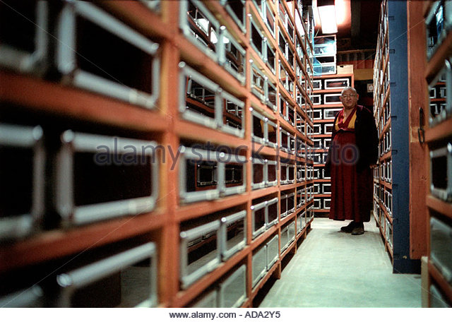 Head of the Bhutan national library looking down the archive of prayer carvings - Stock-Bilder