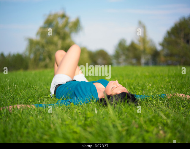 Young woman relaxing in park on green grass - Stock Image