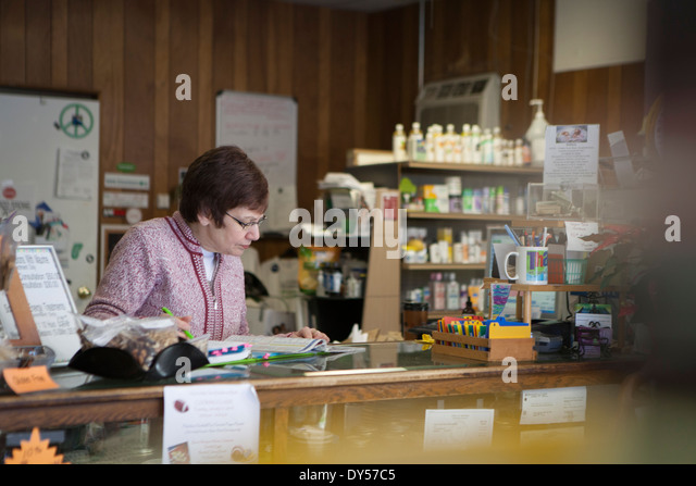Health foods store owner working at counter - Stock Image