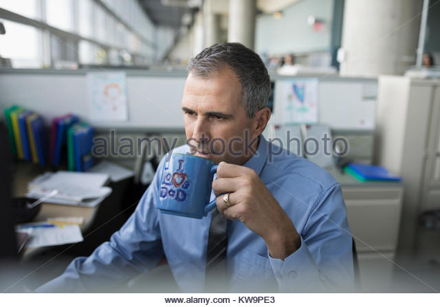 Focused mature businessman drinking coffee from - Stock Image