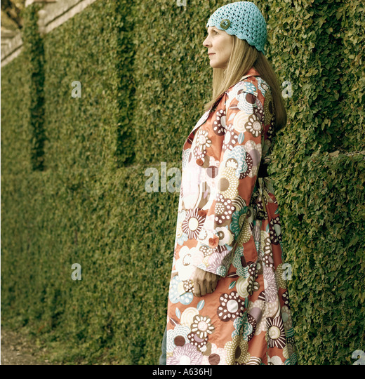Side profile of a young woman wearing an overcoat and a knit hat - Stock Image