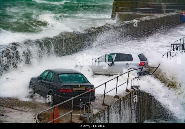 Mousehole, Cornwall, UK. 10th April 2016. UK Weather.  The moment the force of the sea almost pushes this car into - Stock Image