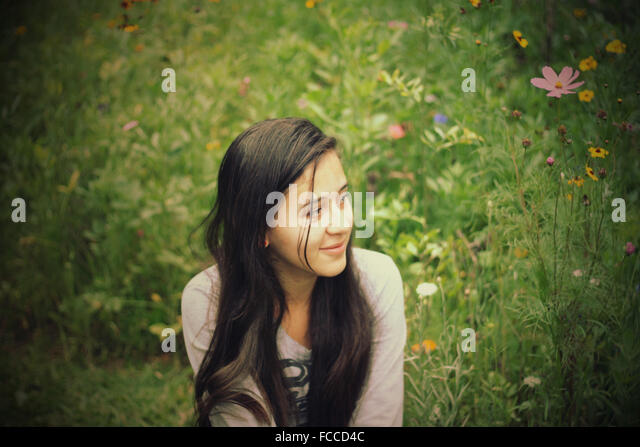 Young Girl Sitting On Meadow - Stock Image