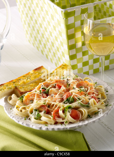 Shrimp pasta with vegetables topped with parmesan cheese served with garlic bread and a glass of white wine - Stock Image