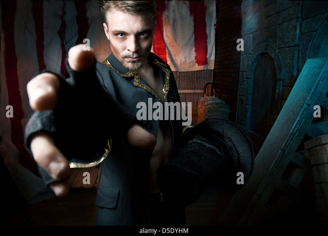 Man in reaching towards viewer in dark tented alley - Stock Image