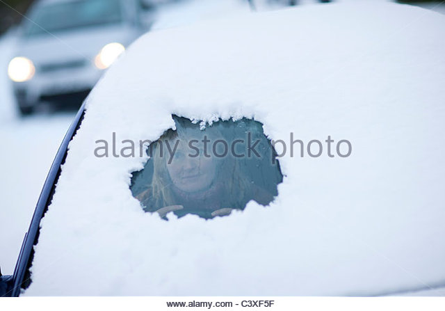 Woman peering from hole in snow on car windshield - Stock Image